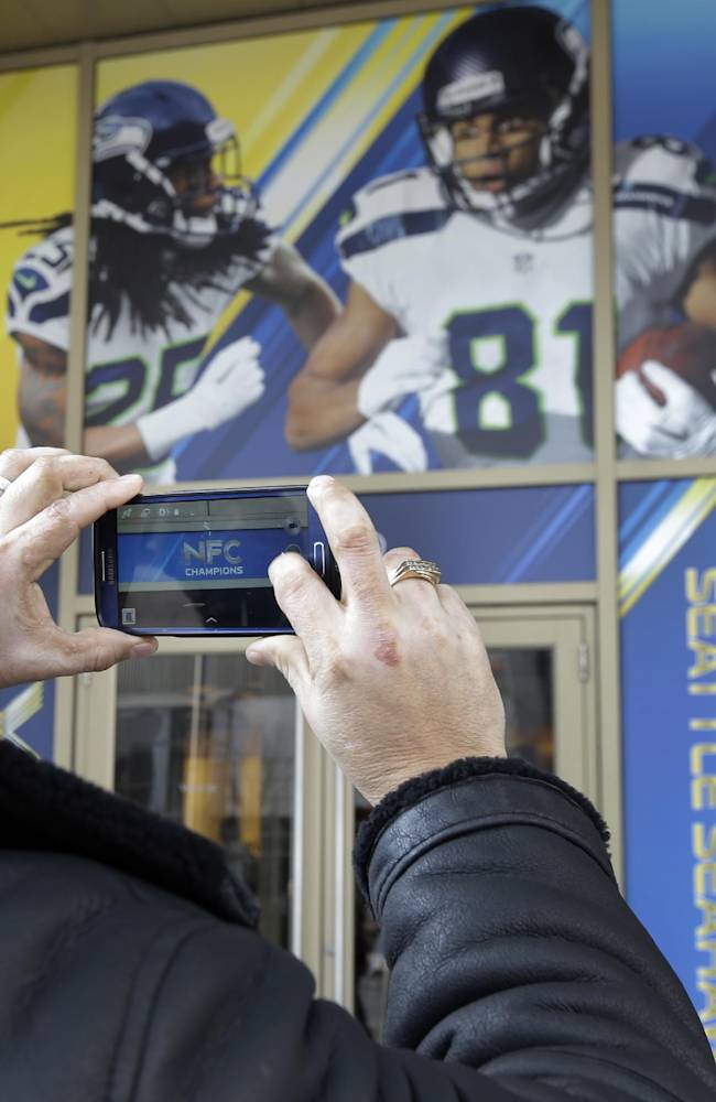 Football fan Raul Moreno of Jersey City, N.J., stops to take a picture of the entrance to the Seattle Seahawks team hotel Monday, Jan. 27, 2014, in Jersey City, N.J. Moreno says he will be rooting for the Denver Broncos when they play the Seattle Seahawks in the Super Bowl XLVIII football game