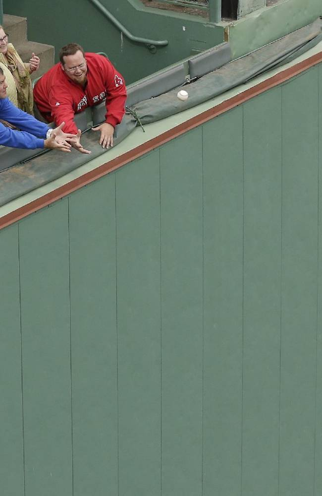 Fans try to catch balls hit over the Green Monster left field wall as the St. Louis Cardinals take batting practice Tuesday, Oct. 22, 2013, in Boston. The Cardinals are scheduled to play the Boston Reds Sox in Game 1 of baseball's World Series on Wednesday