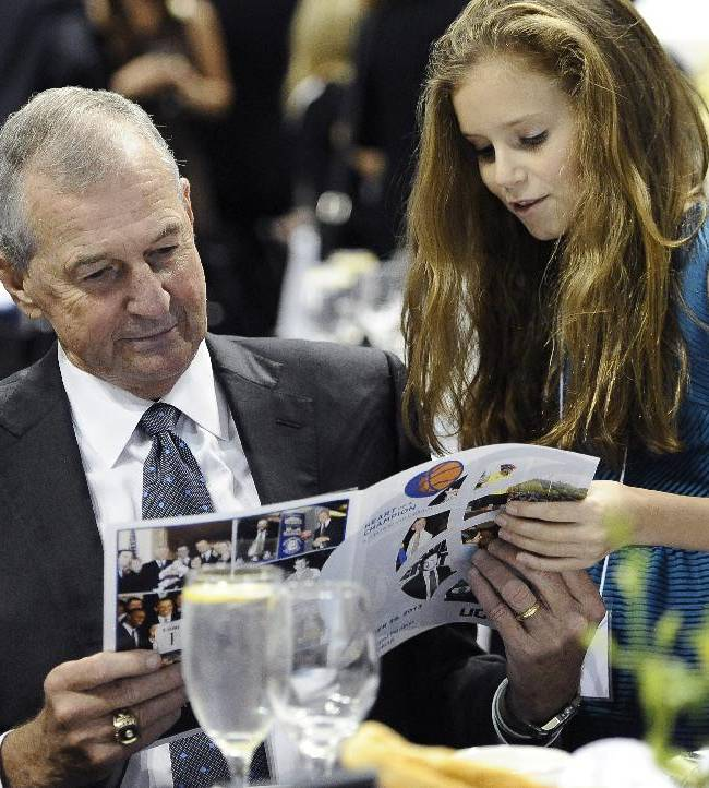 Former Connecticut basketball coach Jim Calhoun looks over a program with his granddaughter Katie Calhoun during a reception honoring his coaching career at the University of Connecticut, Sunday, Sept. 22, 2013 in Storrs, Conn. Calhoun retired a year ago with 873 wins and 380 losses after 40 seasons as a head coach, 26 of them at Connecticut