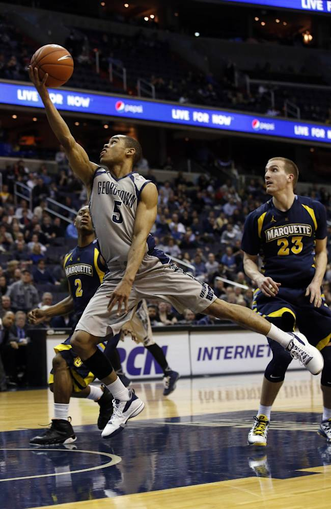 Georgetown guard Markel Starks (5) shoots between Marquette guards John Dawson (2) and Jake Thomas (23) during the second half of an NCAA college basketball game, Monday, Jan. 20, 2014, in Washington. Starks had 28 points, but Marquette won 80-72 in overtime