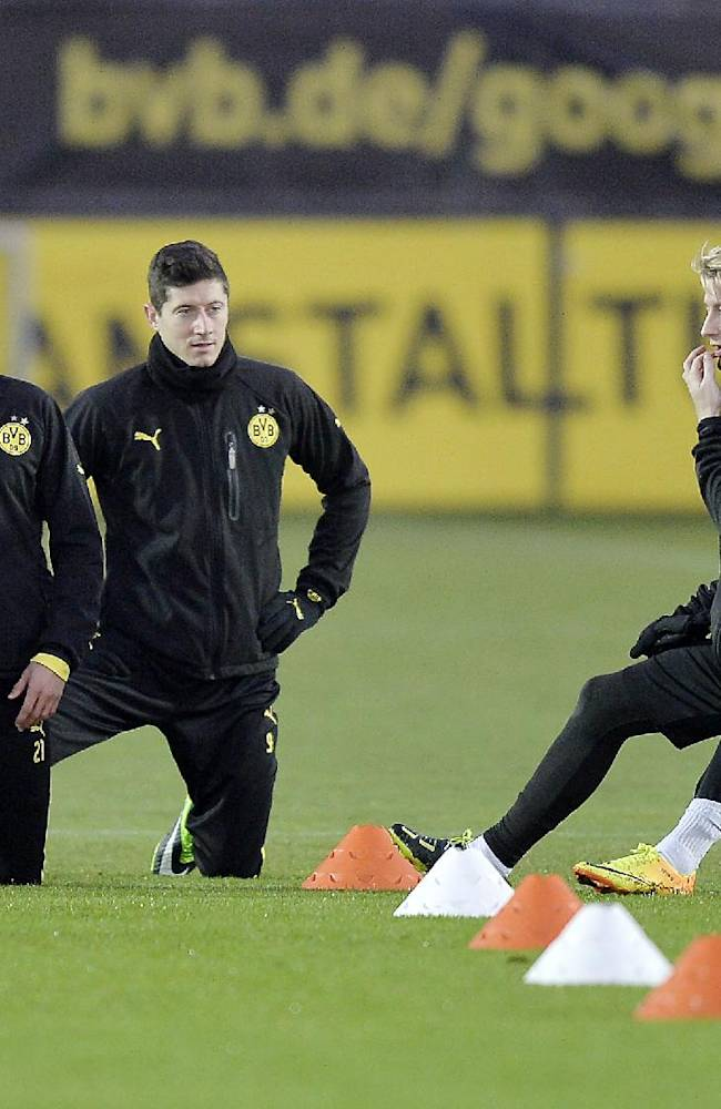Dortmund's Oliver Kirch, Robert Lewandowski and Marco Reus, from left, exercise during a training session prior the Champions League Group F soccer match between Borussia Dortmund and SSC Napoli in Dortmund, Germany, Monday, Nov. 25, 2013