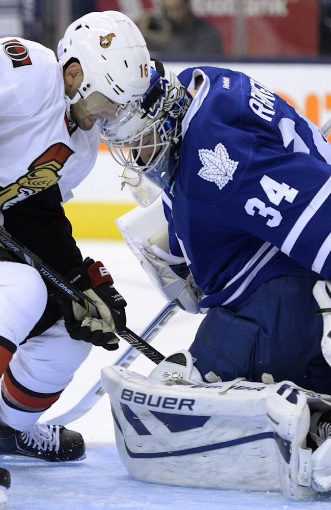 Ottawa Senators' Clarke MacArthur, left, watches as a shot by teammate Cory Conacher (not shown) scores on Toronto Maple Leafs goalie James Reimer, right, during first-period NHL hockey game action in Toronto, Saturday, Oct. 5, 2013