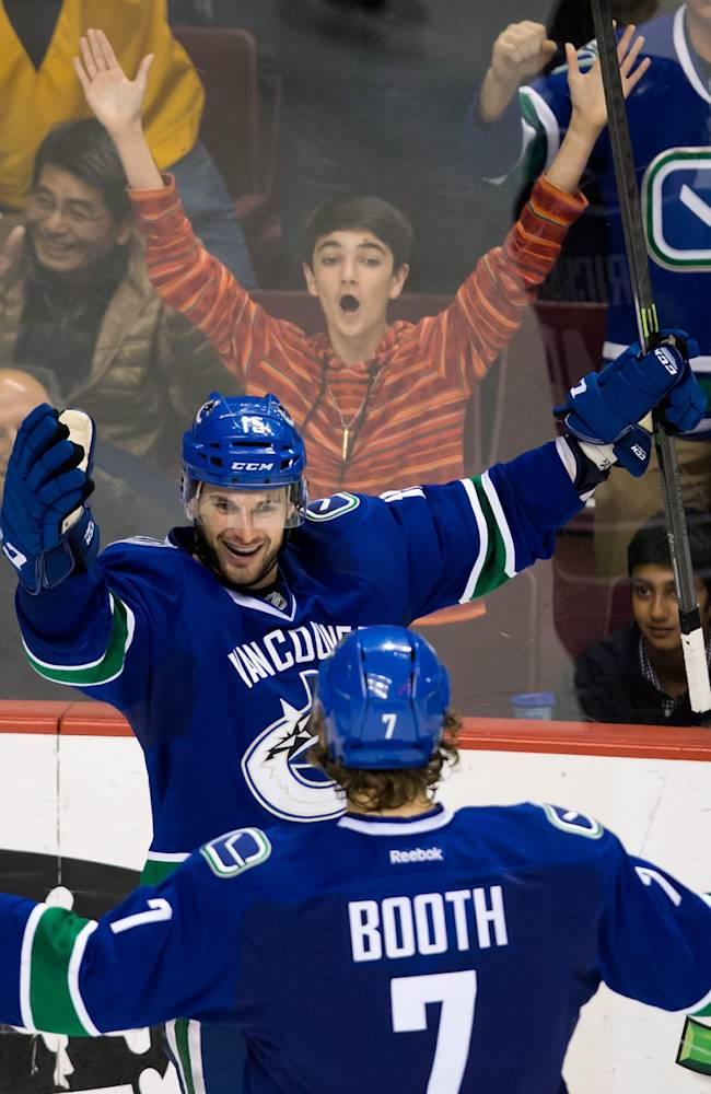 Vancouver Canucks' Brad Richardson, top, and David Booth celebrate Richardson's goal against the Los Angeles Kings during the third period of an NHL hockey game Saturday, April 5, 2014, in Vancouver, British Columbia. Vancouver won 2-1
