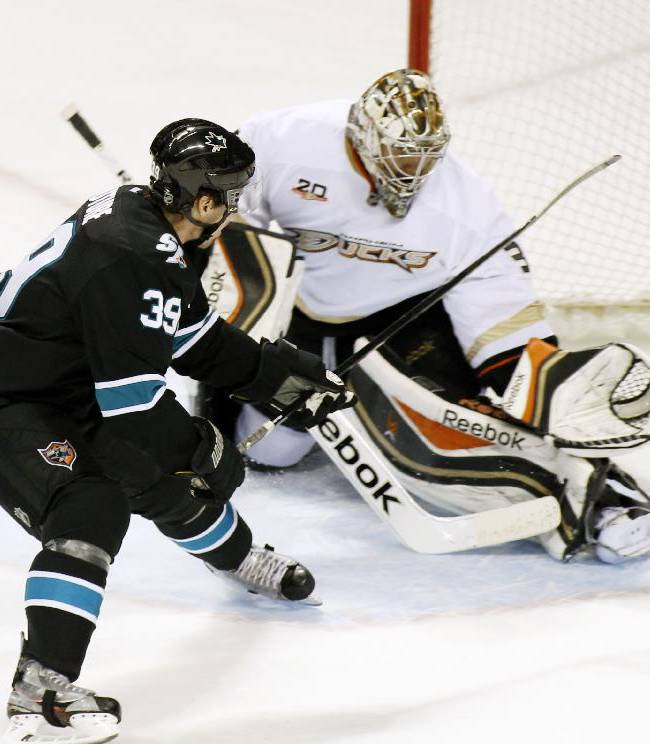 San Jose Sharks' Logan Couture, left, scores a goal past Anaheim Ducks goalie Frederik Andersen, during the first period of an NHL hockey game, Sunday, Dec. 29, 2013, in San Jose, Calif