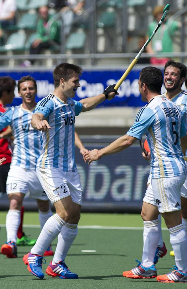 Argentina's Gonzales Peillat, center, cheers with his teammates after Argentina scored the second goal during the Field Hockey World Cup match against Korea in The Hague, Netherlands, Sunday June 8, 2014