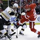 Boston Bruins defenseman Zdeno Chara (33) of the Czech Republic and Detroit Red Wings left wing Drew Miller (20) battle for the puck during the second period of Game 3 of a first-round NHL hockey playoff series in Detroit, Tuesday, April 22, 2014. (AP Photo/Carlos Osorio)