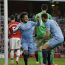Manchester City's David Silva, left, celebrates scoring a goal with Edin Dzeko during the English Premier League soccer match between Arsenal and Manchester City at the Emirates stadium in London, Saturday, March 29, 2014