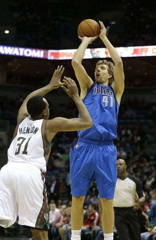 Dallas Mavericks' Dirk Nowitzki(41) puts up a shot against Milwaukee Bucks' John Henson during the first half of an NBA basketball game Saturday, Nov. 9, 2013, in Milwaukee