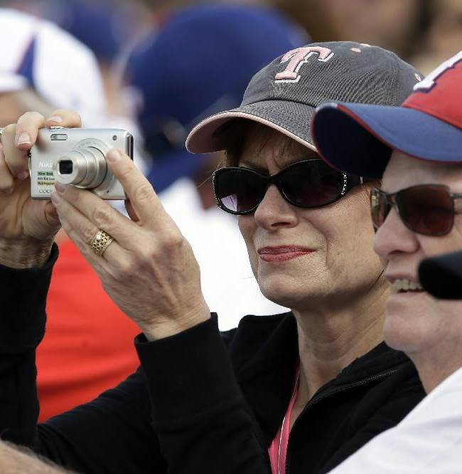 A fan holds up her camera as the Texas Rangers take the field in the fourth inning of a spring training baseball game against the Chicago White Sox, Sunday, March 2, 2014, in Surprise, Ariz
