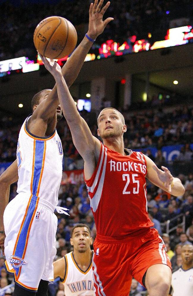 Houston Rockets forward Chandler Parsons (25) drives to the basket around Oklahoma City Thunder forward Kevin Durant during the first quarter of an NBA basketball game, Sunday, Dec. 29, 2013, in Oklahoma City