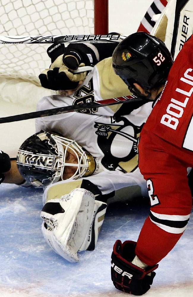 Pittsburgh Penguins goalie Tomas Vokoun, left, can't save a goal by Chicago Blackhawks' Brandon Bollig (52) during the third period of an NHL preseason hockey game in Chicago, Thursday, Sept. 19, 2013. The Penguins won 4-3