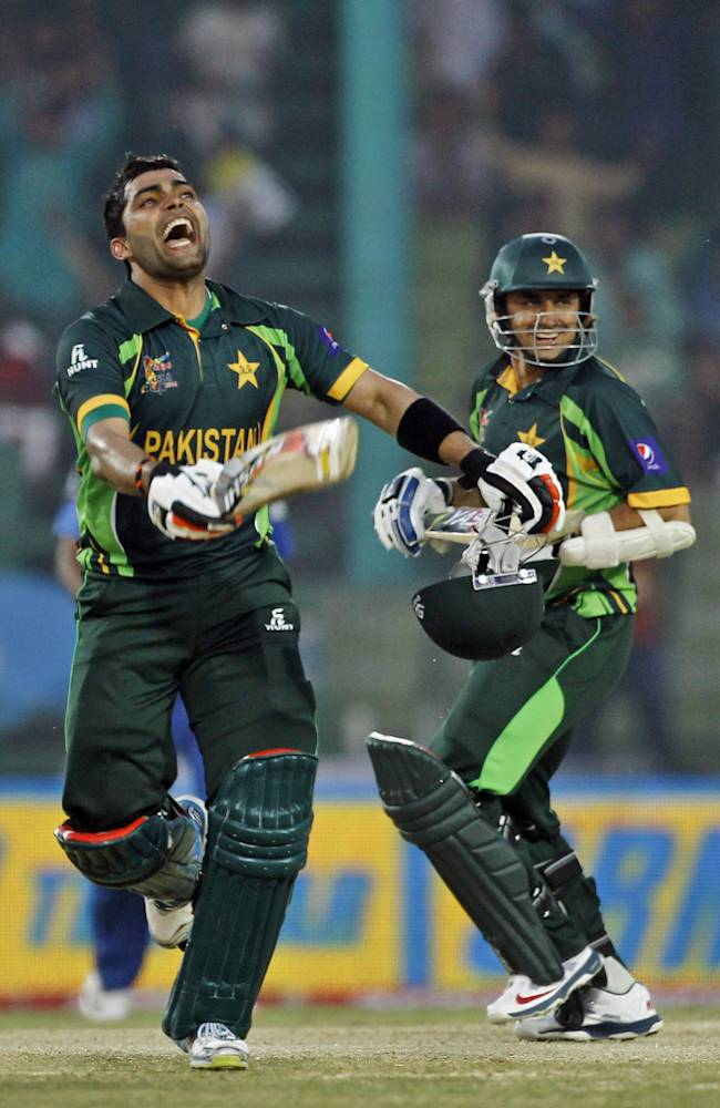 Pakistan's Umar Akmal, left, celebrates after scoring a century as his teammate Saeed Ajmal, right, smiles during the Asia Cup one-day international cricket tournament against Afghanistan in Fatullah, near Dhaka, Bangladesh, Thursday, Feb. 27, 2014