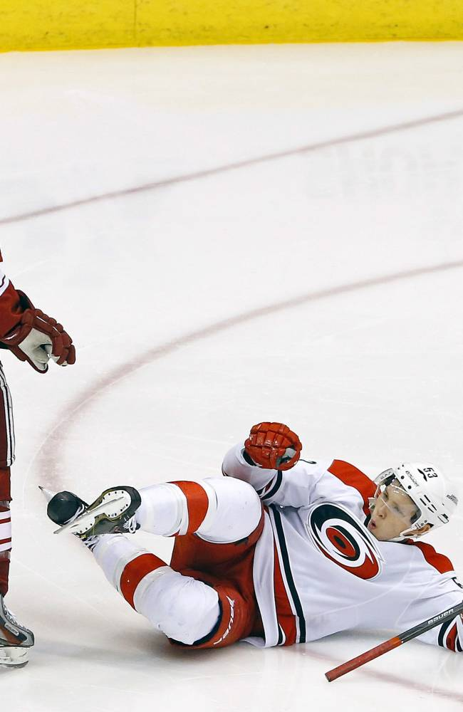 Phoenix Coyotes' Tim Kennedy (34) looks on as Carolina Hurricanes' Jeff Skinner celebrates his goal in the third period of an NHL hockey game Saturday, Dec. 14, 2013, in Glendale, Ariz. The Hurricanes defeated the Coyotes 3-1