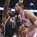 Toronto Raptors' Jonas Valanciunas, right, drives at Milwaukee Bucks' Jeff Adrien during second half NBA basketball action in Toronto on Monday, April 14, 2014 The Associated Press