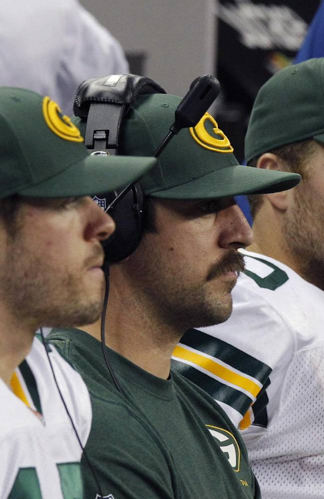 From left, Green Bay Packers' Scott Tolzien (16) sits with quarterback Aaron Rodgers, center, and Matt Flynn, right, on the bench during the second quarter of an NFL football game against the Detroit Lions at Ford Field in Detroit, Thursday, Nov. 28, 2013
