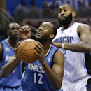 Minnesota Timberwolves' Luc Richard Mbah a Moute (12) looks to shoot as he gets in front of Orlando Magic's Kyle O'Quinn, right, during the first half of an NBA basketball game in Orlando, Fla., Saturday, April 5, 2014 The Associated Press