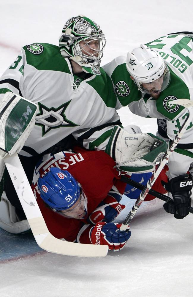 Montreal Canadiens center David Desharnais (51) is sandwiched between Dallas Stars goalie Kari Lehtonen (32) and defenseman Alex Goligoski (33) during the first period of an NHL hockey game Tuesday, Oct. 29, 2013, in Montreal