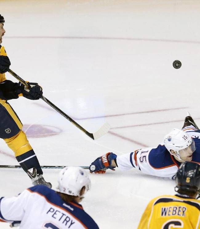 In this Nov. 28, 2013, file photo, Edmonton Oilers defenseman Nick Schultz (15) blocks a shot by Nashville Predators forward Eric Nystrom, left, in the first period of an NHL hockey game in Nashville, Tenn. Shot-blocking is one of the sport's under appreciated skills, but it can come with a price, as in a bruised or broken foot and an absence from the ice for days or weeks
