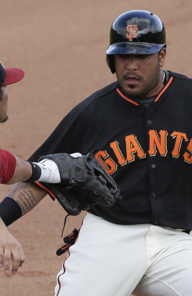 Arizona Diamondbacks third baseman Eric Chavez, left, tags out San Francisco Giants' Hector Sanchez during the fifth inning of a spring training baseball game Sunday, March 2, 2014, in Scottsdale, Ariz
