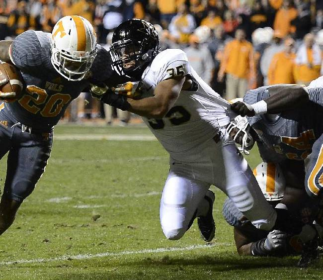 Tennessee running back Rajion Neal (20) runs past Vanderbilt linebacker Darreon Herring (35) scoring from the 5-yard line in the second quarter of an NCAA college football game on Saturday, Nov. 23, 2013, in Knoxville, Tenn