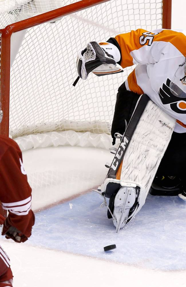 Philadelphia Flyers' Steve Mason (35) gives up a goal to Phoenix Coyotes' Rob Klinkhammer as Coyotes' Mikkel Boedker (89), of Denmark, watches during the second period of an NHL hockey game Saturday, Jan. 4, 2014, in Glendale, Ariz