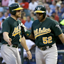 Oakland Athletics' Brandon Moss (37) and Yoenis Cespedes (52) congratulate each other at the plate after scoring on a Seth Smith (15) single in the fourth inning of a baseball game against the Texas Rangers, Monday, June 17, 2013, in Arlington, Texas. (AP Photo/Tony Gutierrez)