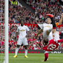 Manchester United's Wayne Rooney, bottom right, scores against Swansea City during their English Premier League soccer match at Old Trafford Stadium, Manchester, England, Saturday Aug. 16, 2014
