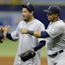 Seattle Mariners' Nelson Cruz, right, and starting pitcher Felix Hernandez, center, celebrate with teammates after the team's 3-0 win over the Tampa Bay Rays during a baseball game Wednesday, May 27, 2015, in St. Petersburg, Fla. Hernandez pitched a complete game shutout and Cruz hit a three-run home run. (AP Photo/Chris O'Meara)