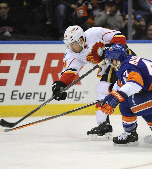 Calgary Flames' David Jones (54) shoots the puck towards the net ahead of New York Islanders' Andrew MacDonald (47) in the first period of an NHL hockey game, Thursday, Feb. 6, 2014, in Uniondale, N.Y
