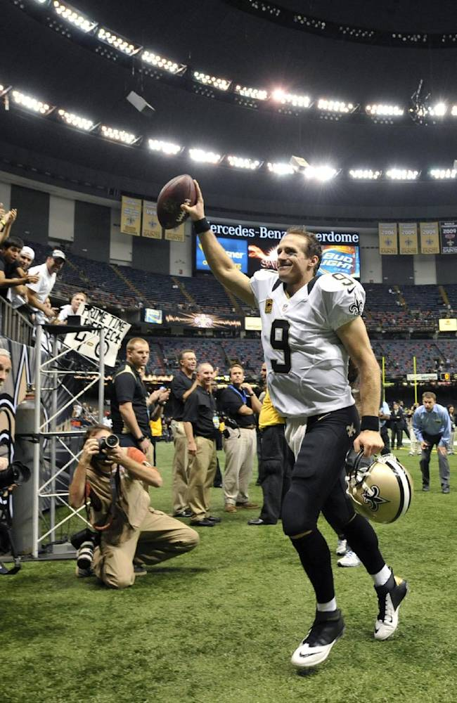 New Orleans Saints quarterback Drew Brees (9) responds to the crowd as he walks off the field after an NFL football game against the Miami Dolphins in New Orleans, Monday, Sept. 30, 2013. The Saints won 38-17