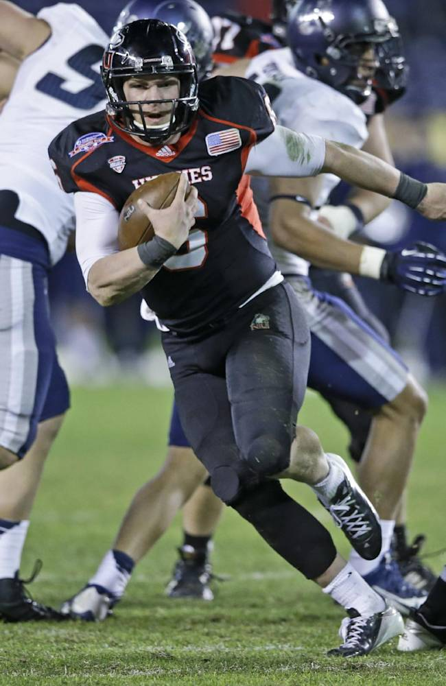 Northern Illinois quarterback Jordan Lynch makes a break against the Utah State defense during the second half of the Poinsettia Bowl NCAA college football game Thursday, Dec. 26, 2013, in San Diego. Utah State won the game 21-14 and Lynch was held to 39 yards rushing