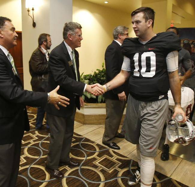 Alabama quarterback AJ McCarron (10) is greeted by members of the Sugar Bowl Committee at a hotel following practice on Friday, Dec. 27, 2013 in New Orleans. Alabama faces Oklahoma in the Sugar Bowl NCAA college football game on Jan. 2