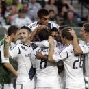 Teammates mob Los Angeles Galaxy midfielder David Beckham (not visible in middle of crowd) after he scores his second goal during the first half of their MLS soccer game, Saturday, July 14, 2012, in Portland, Ore. (AP Photo/Don Ryan)