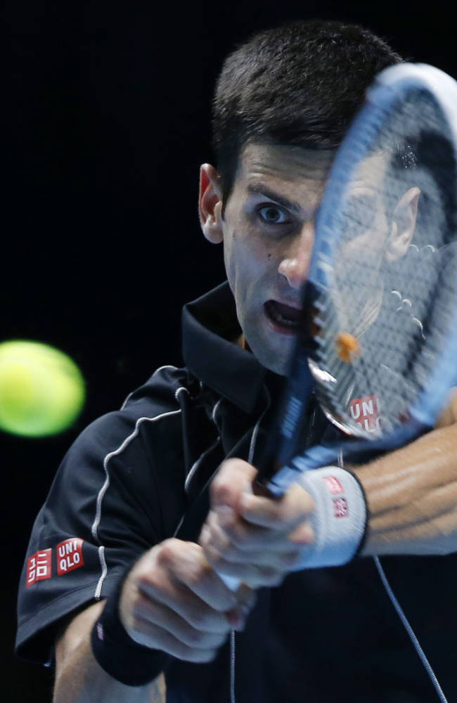 Novak Djokovic of Serbia plays a return to Roger Federer of Switzerland during their ATP World Tour Finals single tennis match at the O2 Arena in London, Tuesday, Nov. 5, 2013
