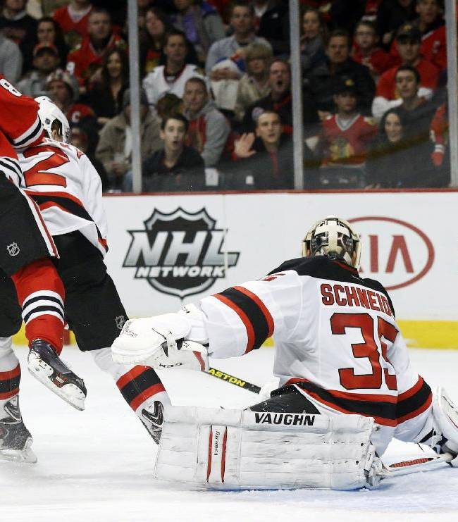 Chicago Blackhawks right wing Patrick Kane, left, scores past New Jersey Devils goalie Cory Schneider (35) during the second period of an NHL hockey game Monday, Dec. 23, 2013, in Chicago