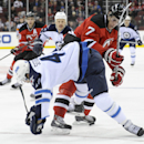 New Jersey Devils' Mark Fayne (7) checks Winnipeg Jets' Devin Setoguchi during the first period of an NHL hockey game Monday, Nov. 25, 2013, in Newark, N.J The Associated Press