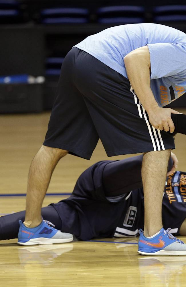 Charlotte Bobcats' Jeffery Taylor, bottom, is stretched by Matt Friia, top, after a practice at the NBA basketball team's training camp in Asheville, N.C., Wednesday, Oct. 2, 2013