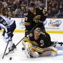 Boston Bruins goalie Tuukka Rask, bottom right, and defenseman Dougie Hamilton clear the puck away from Winnipeg Jets' Mark Scheifele (55) during the third period of the Boston Bruins 2-1 overtime win over the Winnipeg Jets in an NHL hockey game in Boston, Friday, Nov. 28, 2014. (AP Photo/Winslow Townson)