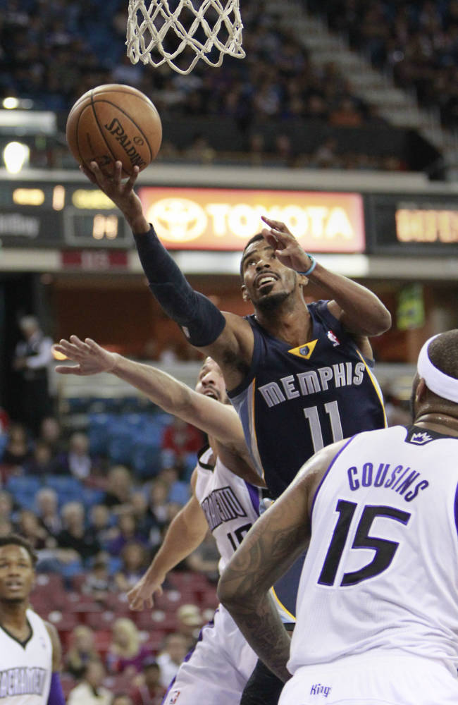 Memphis Grizzlies guard Mike Conley, center, drives to the basket between Sacramento Kings' Greivis Vasquez, , left, of Venezuela and DeMarcus Cousins during the first quarter of an NBA basketball game in Sacramento, Calif., Sunday, Nov. 17, 2013