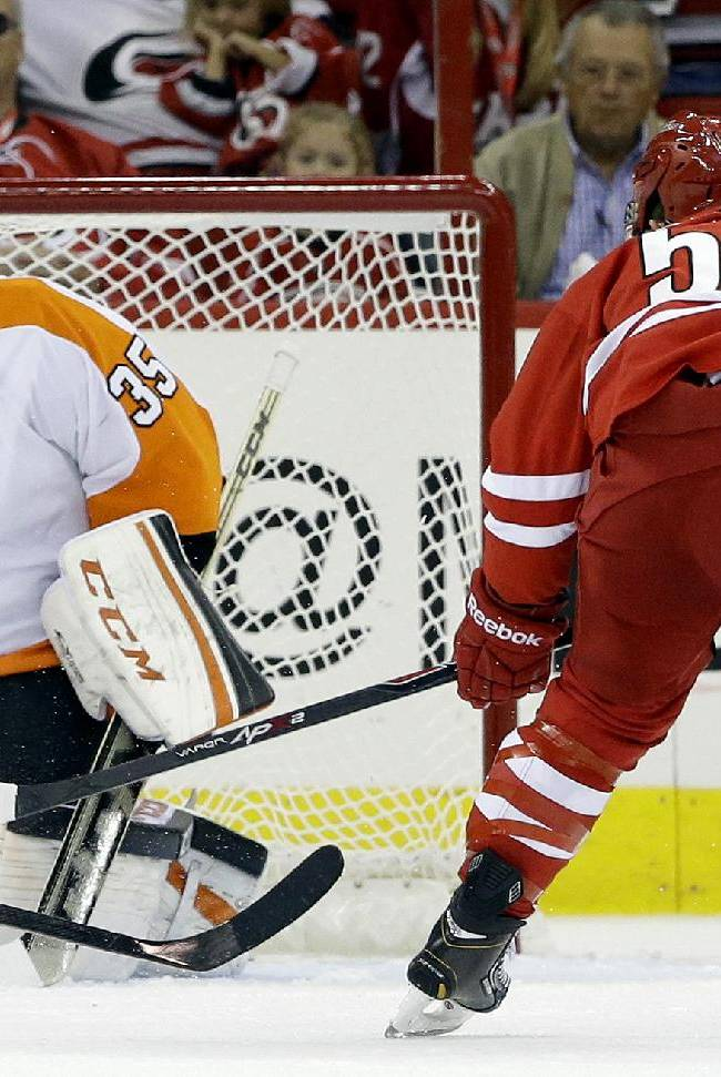 Philadelphia Flyers goalie Steve Mason (35) deflects a shot on goal by Carolina Hurricanes' Jeff Skinner (53)during the first period of an NHL hockey game in Raleigh, N.C., Sunday, Oct. 6, 2013. The Hurricanes won 2-1
