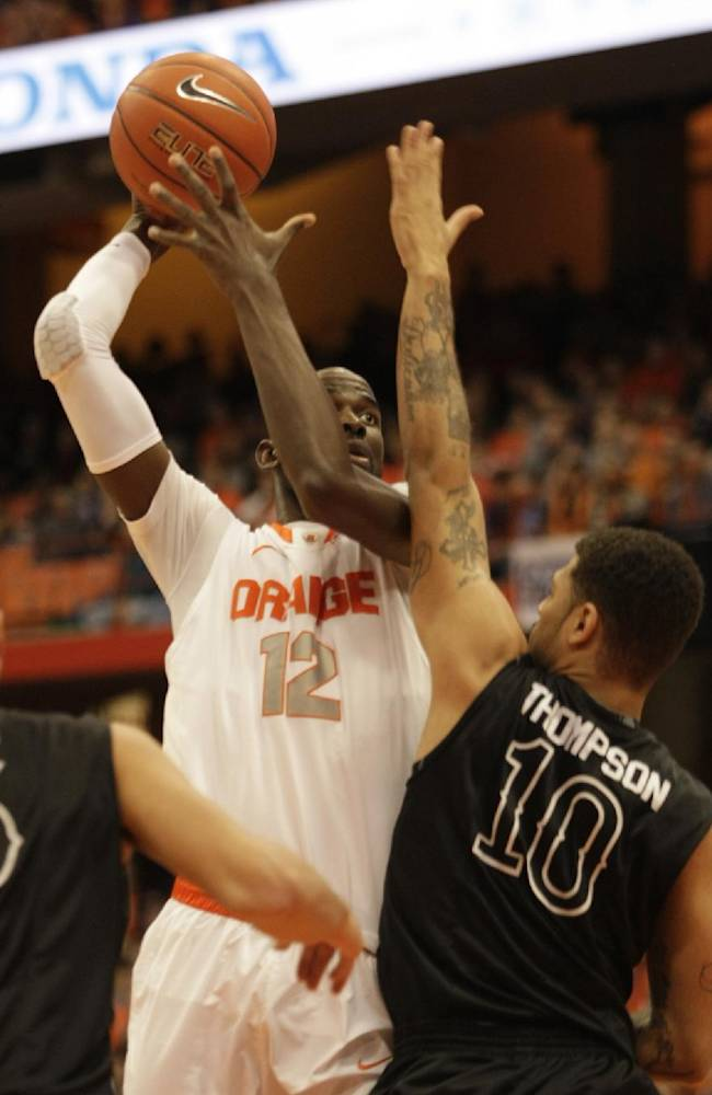 Syracuse's Baye Moussa Keita (12) shoots over High Point's Tarique Thompson, right, in the first half of an NCAA college basketball game in Syracuse, N.Y., Friday, Dec. 20, 2013