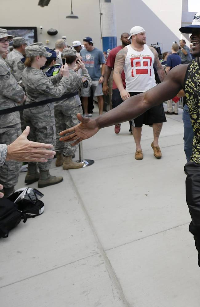 Seattle Seahawks running back Christine Michael, right, greets troops at Joint Base Lewis-McChord, Wash., Tuesday, Sept. 10, 2013, before a ceremony to transfer the team's 12th Man Flag from U.S. Army soldiers who have returned from Afghanistan to U.S. Air Force air crews who fly cargo planes worldwide