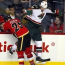 Minnesota Wild's Nate Prosser, right, dodges a check from Calgary Flames' Steve Begin during the first period of their NHL hockey game, Monday, Feb. 11, 2013, in Calgary, Alberta. (AP Photo/The Canadian Press, Jeff McIntosh)