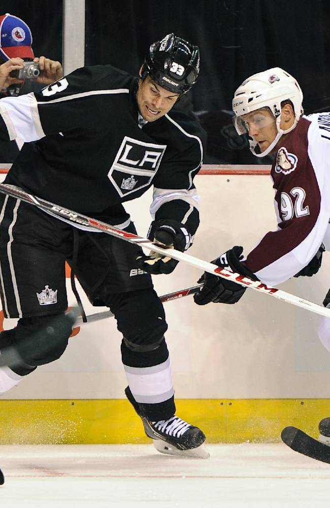 Los Angeles Kings defenseman Willie Mitchell (33) and Colorado Avalanche left wing Gabriel Landeskog (92) fight for the puck in the first period of an NHL preseason hockey game, Saturday, Sept. 28, 2013, in Las Vegas