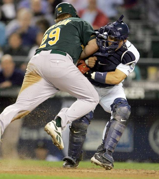 In this Sept. 27, 2006, file photo, Oakland Athletics' Dan Johnson, left, collides with Seattle Mariners' Kenji Johjima at home plate but was out on the play as Johjima held onto the ball in the ninth inning of a baseball game at Safeco Field in Seattle.  New York Mets general manager Sandy Alderson, chairman of the rules committee, announced Wednesday, Dec. 11, 2013, that Major League Baseball plans to eliminate home plate collisions. He said player health and increased awareness of concussions were behind the decision