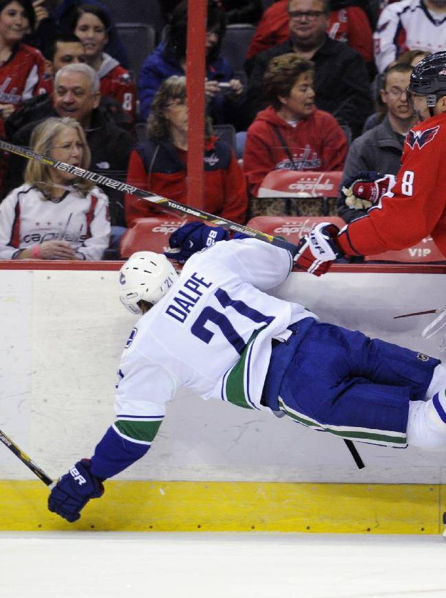 Washington Capitals right wing Alex Ovechkin (8), of Russia, knocks down Vancouver Canucks center Zac Dalpe (21) during the first period of an NHL hockey game, Friday, March 14, 2014, in Washington
