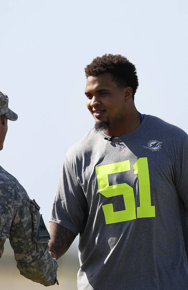 Miami Dolphins center Mike Pouncey (51) shakes hands with a service member during an NFL Pro Bowl practice on Earhart Field at Joint Base Pearl Harbor-Hickam sponsored by the USAA the official military sponsor of the NFL on Thursday January 23, 2014 in Honolulu, Hawaii. (Aaron M. Sprecher/AP Images for USAA)