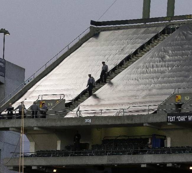 Law enforcement officials walk in the upper deck of O.co Coliseum after an NFL football game between the Oakland Raiders and the Tennessee Titans in Oakland, Calif., Sunday, Nov. 24, 2013. Authorities say a football fan jumped after the game from the third deck of the Oakland Coliseum, injuring herself and a man one level below who tried to catch her. She and the man who tried to catch her were rushed to the hospital for treatment