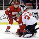 Florida Panthers goalie Tim Thomas (34) deflects a shot on goal by Detroit Red Wings center Cory Emmerton (25) during the first period of an NHL hockey game in Detroit, Saturday, Dec. 7, 2013. (AP Photo/Carlos Osorio)