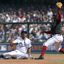 The Los Angeles Dodgers' Andre Ethier, center, is tagged out at second by the Arizona Diamondbacks' Didi Gregorius during the second game of their two-game Major League Baseball opening series at the Sydney Cricket Ground in Sydney, Sunday, March 23, 2014